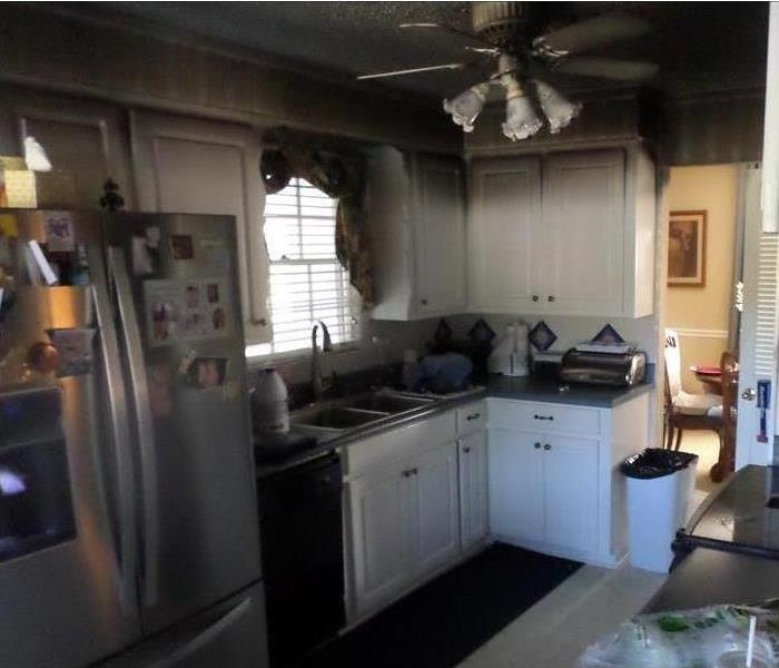 Kitchen in home with heavy soot damage, white cabinets, white tile floors, stainless steel refrigerator