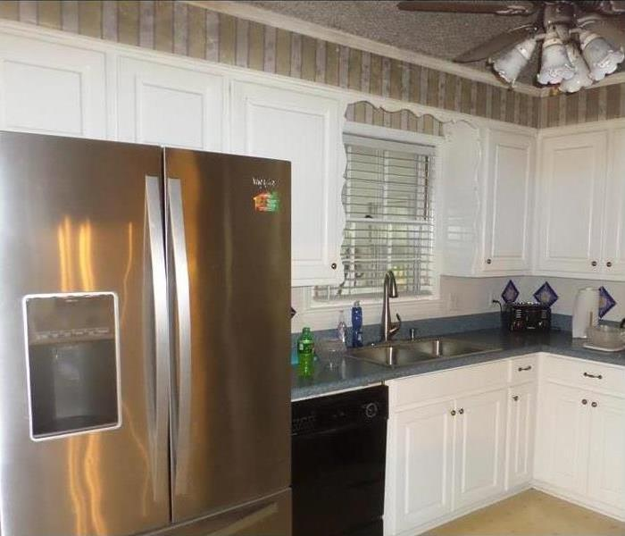 Kitchen in home, wood floors, white cabinets, blue countertops, stainless steel refrigerator