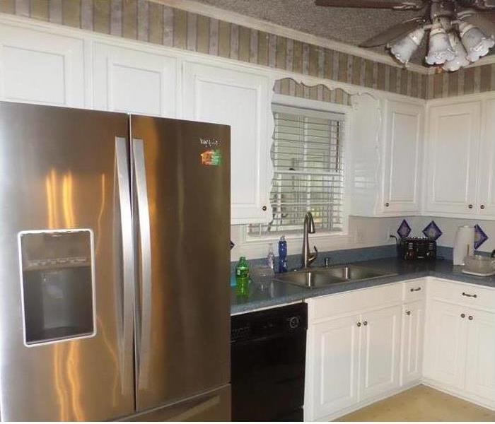 Kitchen in home, white tile floors, white cabinets, blue countertops, stainless steel refrigerator