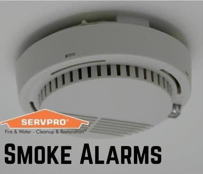 White smoke alarm attached to ceiling with orange SERVPRO logo and smoke alarm written in bold text.